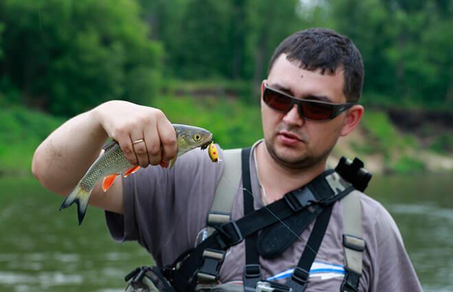 Мужчина ловит рыбу в очках